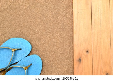 Slippers on wood and sand