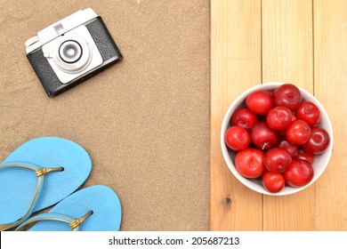 Slippers and plums on wood and sand