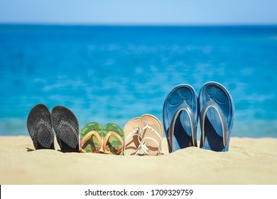 Slippers of the whole family in the sand by the sea on nature while traveling. Rest by the water on vacation with shoes.