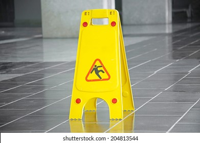 Slippery floor surface warning sign and symbol in building, hall, office, hotel , restaurant, restroom. Concept photo danger.