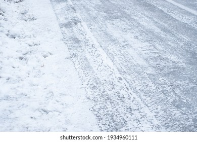 Slippery frozen road covered with ice during winter. Difficult weather conditions. Icy street and sidewalk. Dangerous traffic.