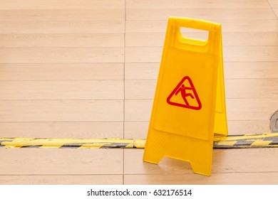 Slippery icon on yellow plastic warning sign alerts for hazard on floor, under construction concept.