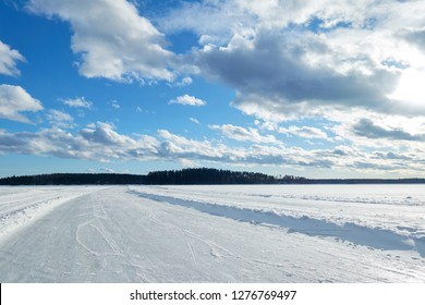 Slippery road on the ice of frozen lake on a sunny winter day in Finland. White snow and clouds on blue sky.Beautifull winter landscape.