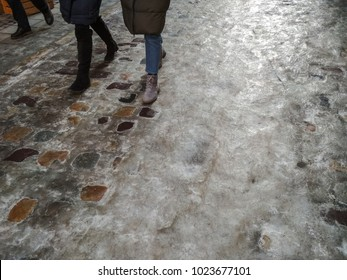 Slippery roads. Legs of people in the street with roads coverd with ice, otop view, copy space