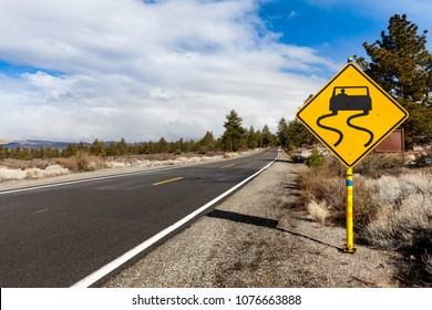 A slippery when wet road sign on the right side of the route 120 that winds through the Eastern Sierras around Mono Lake area warns drivers to be careful when driving.