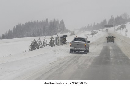 Slippery winter highway causes a vehicle to lose control and flip onto it's side in the highway median