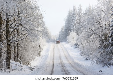 Slippery winter road with a car on a forest road