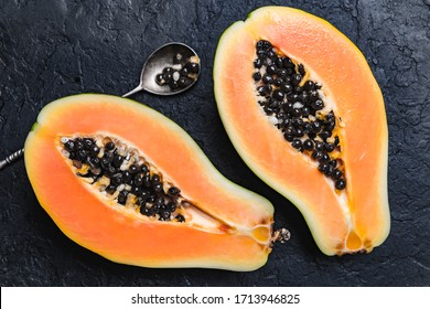 Slised papaya with silver spoon on black concrete background. Food photography
