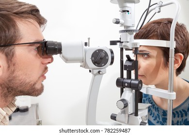 Slit Lamp eye control with the Ophthalmologist pretty woman during an exam with Slit Lamp  the ophthalmologist in eyes clinic doing cornea and retina exam diagnostic  high technology concept eyes care