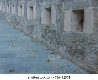 the slits were openings in the wall of the fortress to spy on  and to use the  weapons against the enemy /series of slits of an ancient castle