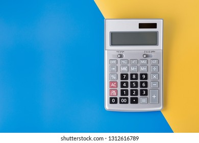 Sliver calculator on blue and yellow background, flat lay with space