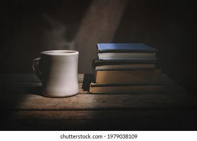 Sliver of light shining on books and mug