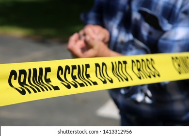 Sliver in a mans finger. An unidentifiable man suffers great pain and suffering while trying to remove a wood sliver from his finger while behind CRIME SCENE DO NOT CROSS yellow caution tape.