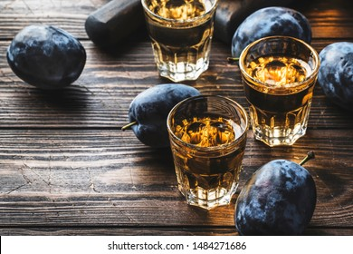 Slivovica - plum brandy or plum vodka, hard liquor, strong drink in glasses on old wooden table, fresh plums, copy space