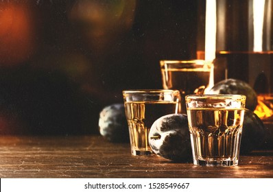 Slivovica - plum brandy or plum vodka, hard liquor, strong drink in glasses on old wooden table, fresh plums, copy space - vintage noise toned