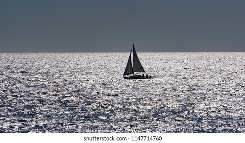 Sloop rigged sailboat under way in a steady breeze, silhouetted in light reflected from afternoon summer sun on the Pacific Ocean in southern California with concepts of speed, freedom, independence