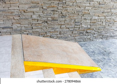 The slope for disabled people wheelchair nearby exterior grey brick wall pattern.