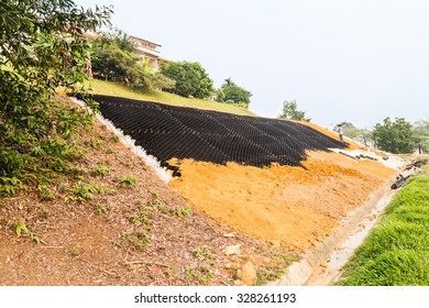 Slope erosion control with grids and earth on steep slope.