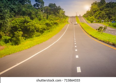 Slope highway with sunshine and green traffic island. Four lane highway with green traffic island. The Provincial immense road passing through a green forest.