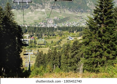 The slope of the ski resort in the late summer. Empty chairs of the funicular. Around green spruce. In the background on the mountainside you can see the Georgian village of Mestia