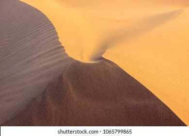 The slopes of a sand dune coming together at the top