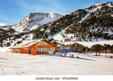 Slopes of Winter Resort El Tarter and Pyrenees Mountains in Andorra. Restaurant and cafe building, unidentified people skiing