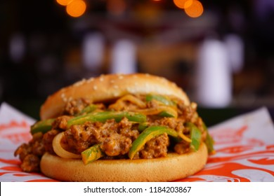 Sloppy burger with sauce in a restaurant background