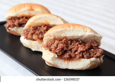 Sloppy Joe Sliders - Three home-made Sloppy Joe slider sandwiches on a black serving tray.