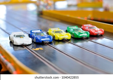 Slot car racing. Five cars with damaged bumpers at the start.