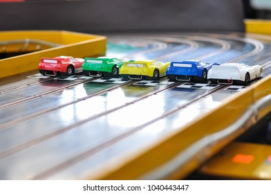 Slot car racing. Five cars with damaged bumpers at the start. Back view