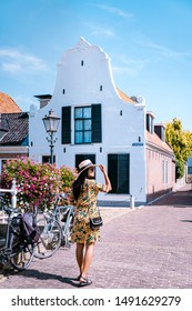 Sloten Friesland Netherlands August 2019, young woman walks at the Streets of Sloten Friesland Netherlands, old historical town with house and canals and boats Sloten