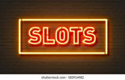 Slots neon sign on brick wall background