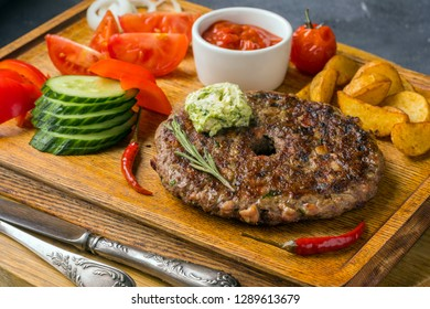 A Slovak meat dishe is on wooden board with tomatoes and fried potatoes, red sauce