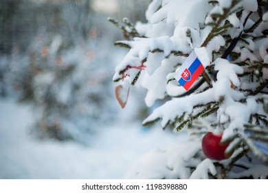 Slovakia flag. Christmas background outdoor. Christmas tree covered with snow and decorations and a flag. Happy New Year and Merry Christmas holiday greeting card.