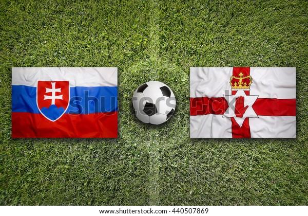 Slovakia vs. Northern Ireland flags on green soccer field