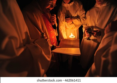 SLOVENIA, EUROPE - Easter vigil (Saturday, 7th April 2012): Catholic priest reading from a roman missal in the dark while altar boys hold a candle.
