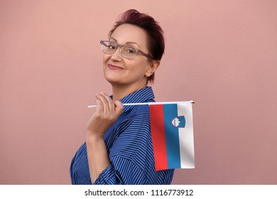 Slovenia flag. Woman holding Slovenian flag. Nice portrait of middle aged lady 40 50 years old with a national flag over pink wall background.Learn Slovenian language. Visit Slovenia concept.
