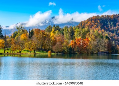 Slovenia, lake Bled view with multi colored autumn trees and mountains with clouds