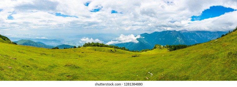 Slovenia mountains near the Kamnik city on Velika Planina pasture land. View of mountains with white clouds and blue sky, mist in the hill. Beautiful and tranquil nature, fresh grass.