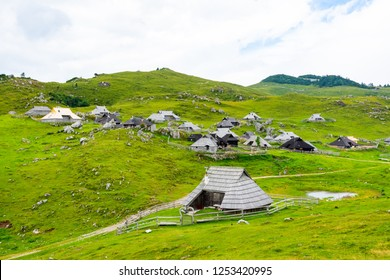 Slovenia velika planina (big plateau), agriculture pasture land near city Kamnik in Slovenian Alps. Wooden houses on green land used by herdsmen. Mountain village with big pasture plateau