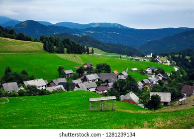Slovenian summer scenic countryside, tall mountains in the background, green grass, forest, blue sky