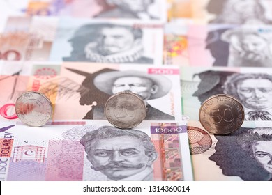 Slovenian tolar coins on the background of banknotes
