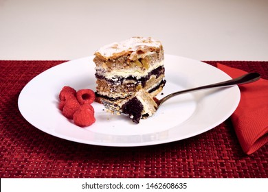 Slovenian tradional layered pastry from province of Prekmurje. (PREKMURSKA GIBANICA).  Cake sits on a white plate with fork and raspberries.