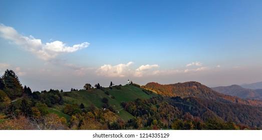 slovenija mountain panorama with little church at sunset