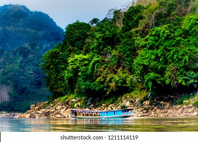 Slow boat cruise on the yellow  Mekong River in Laos, tropical jungle background