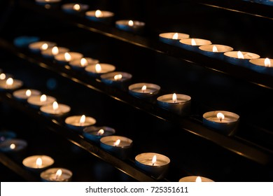 Slow burning wax candles in church as a symbol of death memory. Dark macro close composition with shallow depth of field.