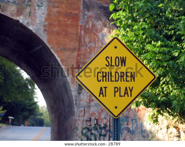 Slow Children at Play road sign with brick tunnel in background