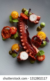 Slow cooked octapus with avocado puree, dehydrated tomatoes, pesto and cooked cherry tomatoes