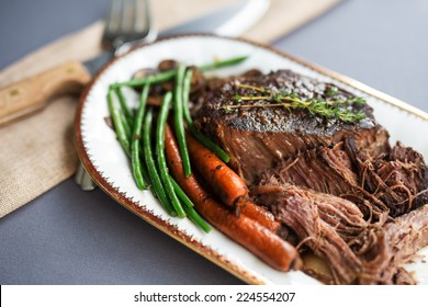 Slow cooked pot roast with carrots, green beans, onions, garlic and gravy on a white porcelain platter with gold rim and serving fork against a gray tablecloth.