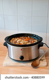 Slow cooker with Lid off and copy space, on a chopping board with wooden spoon